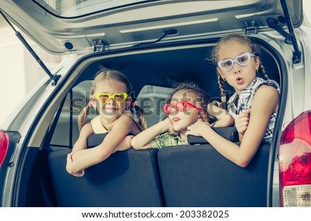 Brother and sisters  sitting in the car near house at the day time - stock photo