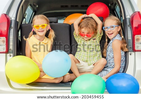 Brother and sisters with balloons sitting in the car at the day time