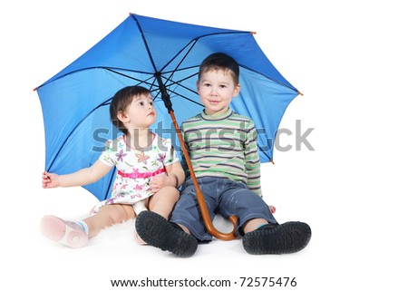 brother and the sister sit under a blue umbrella