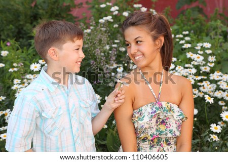 Brother give flower sister near cottage - stock photo