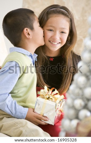 Brother Kissing His Sister On The Cheek,And Holding A Christmas Gift - stock photo