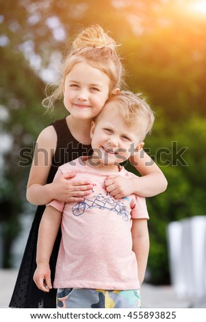 Brother playing with sister in the park - stock photo