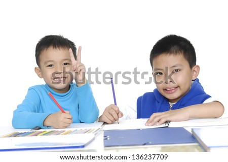 Brother School boy sitting and writing in notebook - stock photo