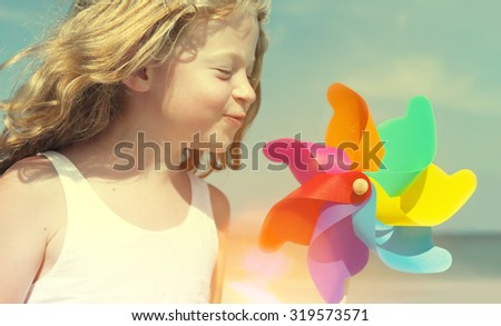 Brother Sister Blowing Windmill Beach Enjoyment Concept - stock photo