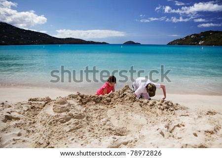 Brother & sister build sandcastles on the beach - stock photo