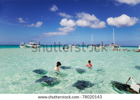 Brother & sister enjoy playing with the stingrays at the sandbar off Grand Cayman - stock photo