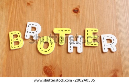BROTHER, spell by woody puzzle letters with woody background - stock photo