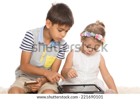 Brother teaches younger sister play on a Tablet PC. Isolated on white. - stock photo