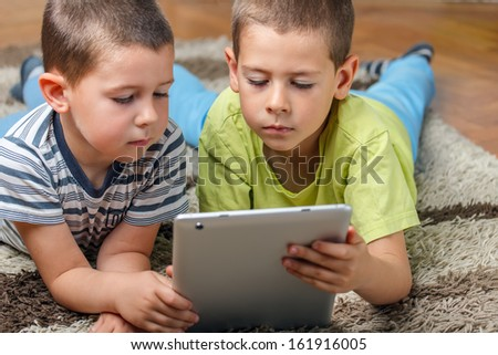 Brother using modern tablet computers - stock photo