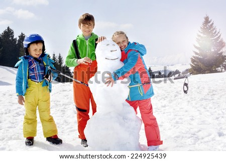 brothers and sister  building a snowman - stock photo