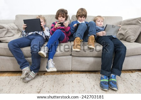 Brothers and sister using electronic devices while slouching on sofa at home - stock photo
