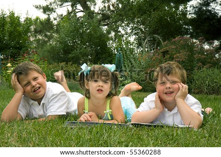 Brothers and their sister enjoying each other's company outdoors - stock photo
