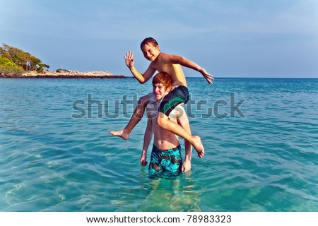 brothers are playing together in a beautiful sea with crystal clear water and blue sky - stock photo