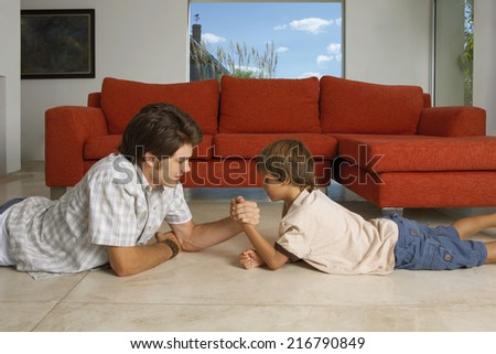 Brothers arm wrestling.