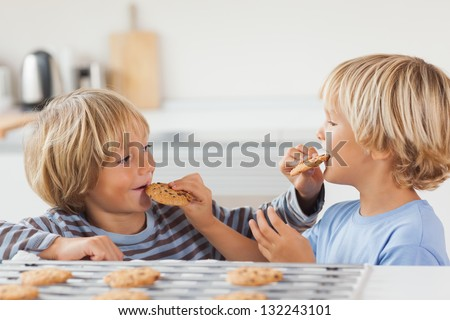 Brothers eating cookies together in the kitchen