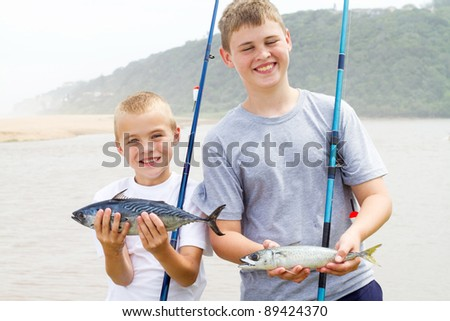 brothers holding two fish and showing their catch of the day - stock photo