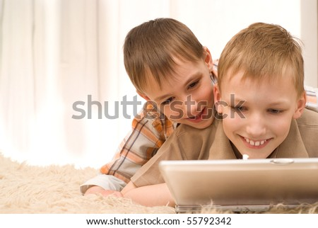 brothers lie on the carpet with laptop - stock photo