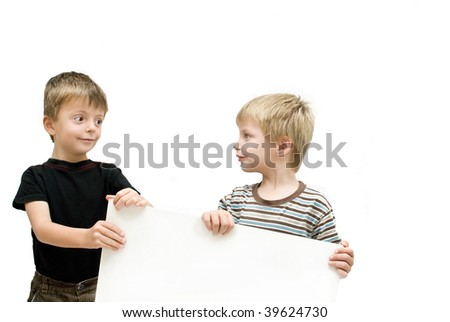 Brothers look at each other whilst holding up a blank poster. - stock photo