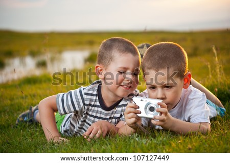 Brothers lying on meadow and taking pic on their camera - stock photo
