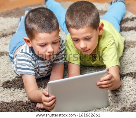 Brothers on the floor using tablet - stock photo