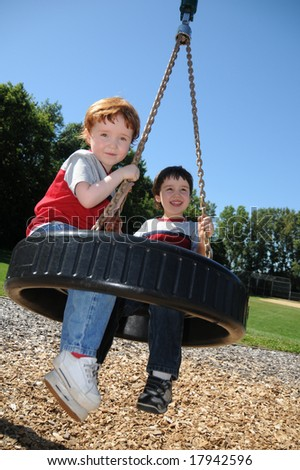 Brothers on tire swing - stock photo