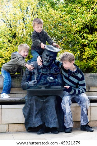 Brothers playing around a statue in a park. - stock photo