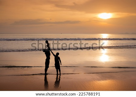 Brothers playing in the sea and the sunset.