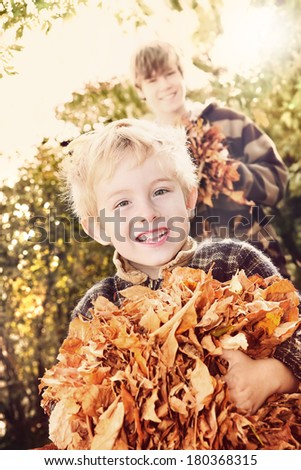 Brothers playing with autumn leaves - stock photo