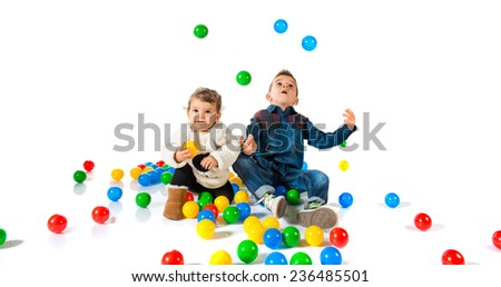 Brothers playing with colored balls - stock photo
