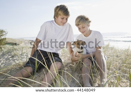 Brothers playing with dog at the beach - stock photo
