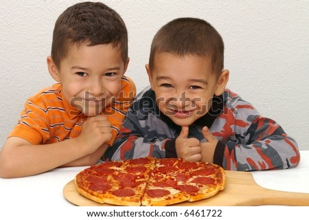 Brothers ready to eat a pepperoni pizza - stock photo