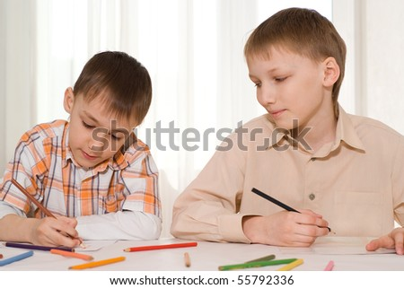 brothers sit at the table and draw