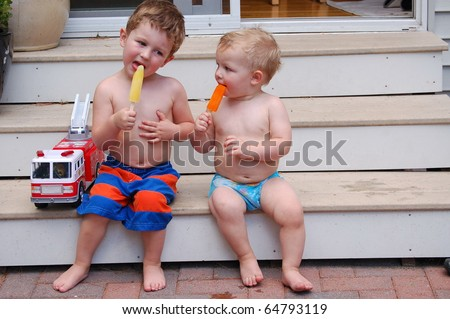 Brothers sit on step and enjoy summer treat/Enjoy the Moment/Take time to enjoy each day - stock photo