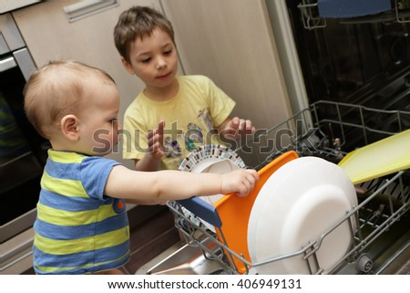 Brothers take the dishes out of the dishwasher - stock photo