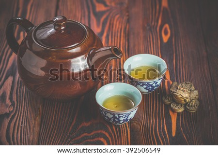 Broun ceramic teapot and two cups for the tea ceremony on rustic wooden table - stock photo