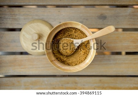 Brow sugar in wooden sugar bowl on wood background - stock photo