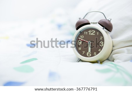 brown alarm clock on bed