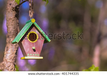 Brown and green birdhouse hanging from tree branch with foliage blurred in background - stock photo
