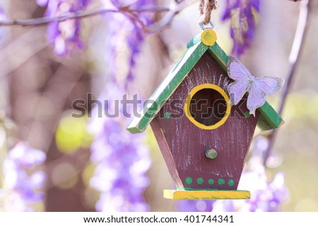 Brown and green birdhouse with purple butterfly hanging from tree branch with blurred purple spring flowers blurred in background - stock photo