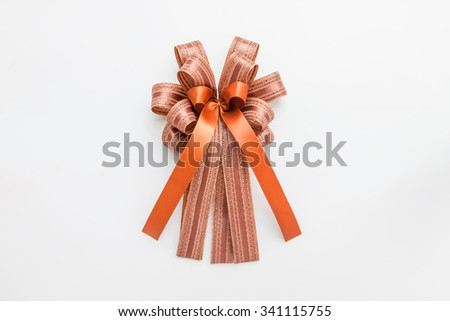 Brown and orange ribbon with bow on white background for christmas and new year - stock photo