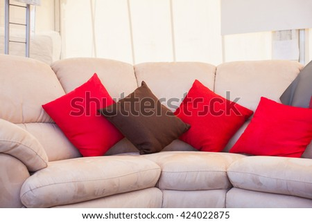 Brown and red pillows on sofa - stock photo
