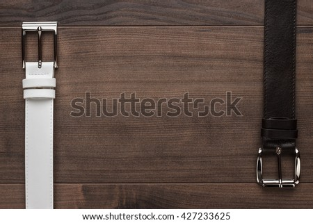 brown and white men's leather belts on wooden table - stock photo