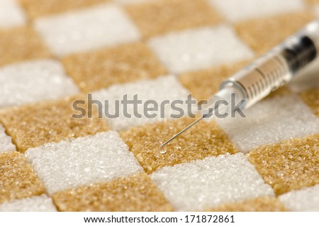 Brown  and white sugar cubes arranged checker shape and a syringe for insulin  - stock photo