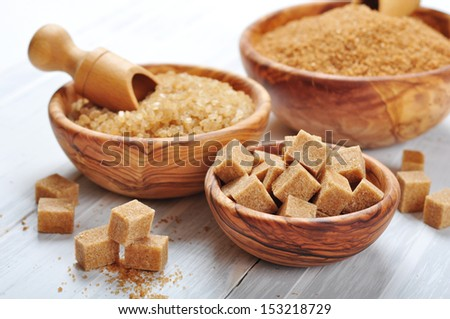 brown and white sugar in wooden bowls closeup