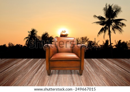 Brown antique leather chairs on the wood decking at the rear view into the sunset - stock photo