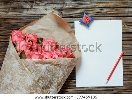 Brown bag of freshly gathered pink stemmed roses next to blank white paper and colored pencil over weathered wooden background - stock photo