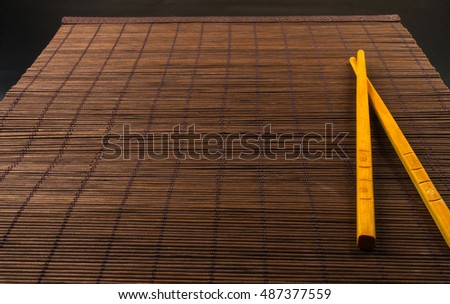 brown bamboo Mat with chopsticks - stand food, close-up, macro