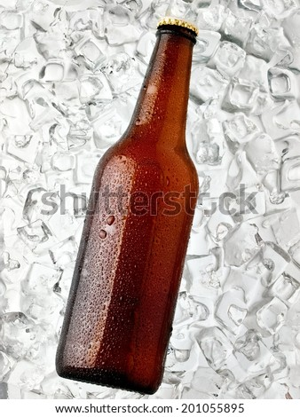 Brown beer bottle with drops on ice, top view - stock photo