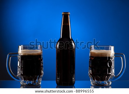 Brown beer bottle with two mugs on blue background - stock photo