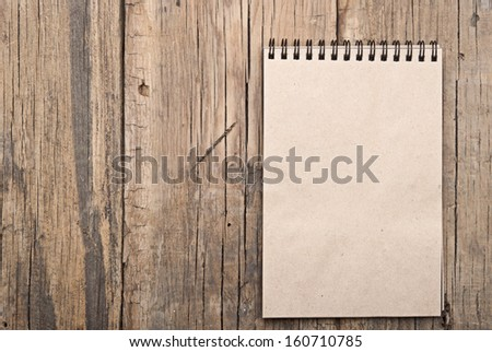 brown blank note book on grunge wood  - stock photo